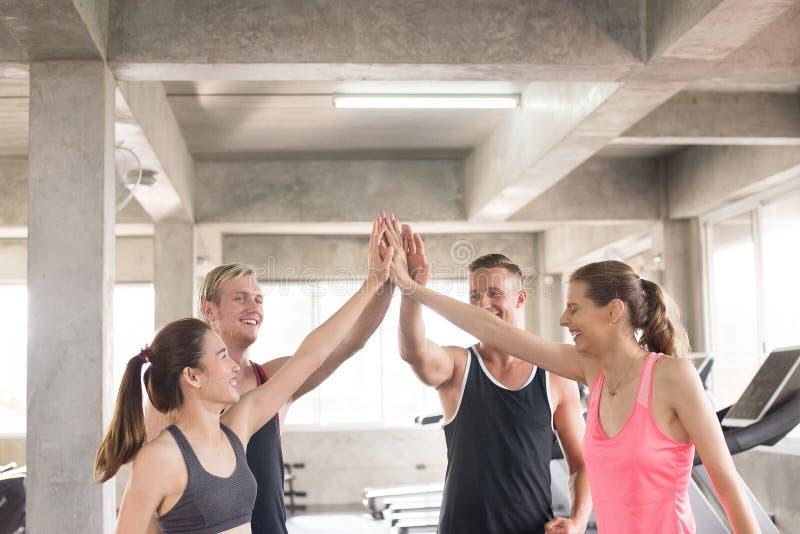 Das lächelnde sportliche Team, das attraktiv ist und klatschen oder schließen sich Hände zusammen an, Handkoordination von den mo stockfotografie