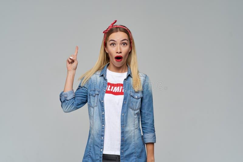 Das langhaarige attraktive blonde Mädchen hebt enthusiastisch ihren Finger oben an und schreit Eureka, weit Öffnung ihr Mund lizenzfreie stockfotografie