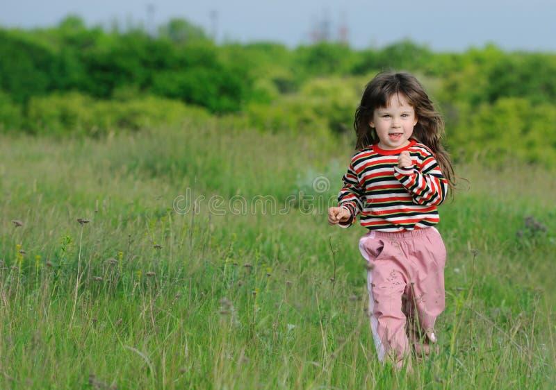 Das laufende Mädchen auf einem grünen Feld stockfotografie