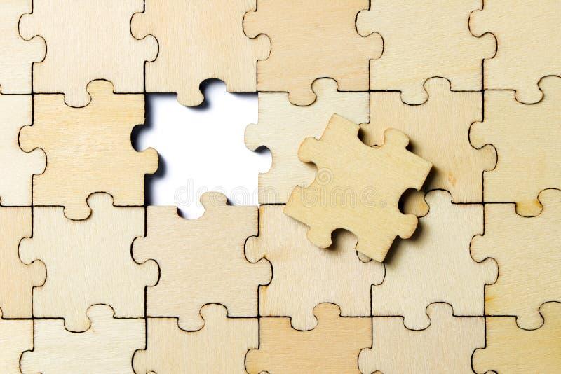 Das letzte Stück eines zackigen hölzernen Puzzlespiels stockfotografie