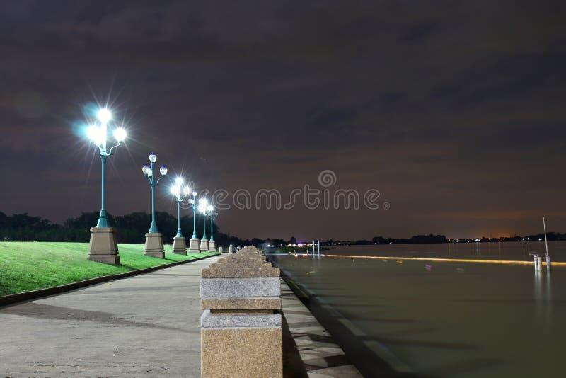 Das Licht von einem hellen Pfosten nachts im Park bei Riverwalk Beleuchtung, Sitzplätze, Abendfluchtlandschaft lizenzfreie stockbilder
