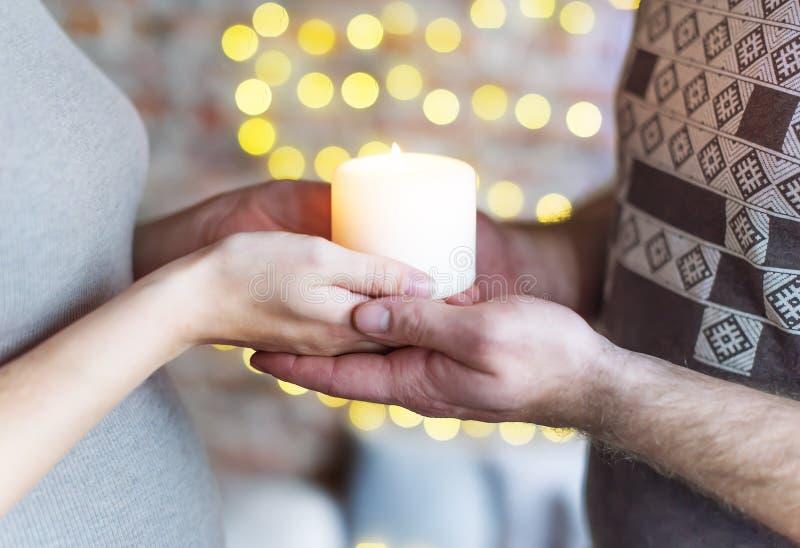 Das liebevolle Paar hält die brennende Kerze in der Hand Die Frau ist schwanger stockbilder