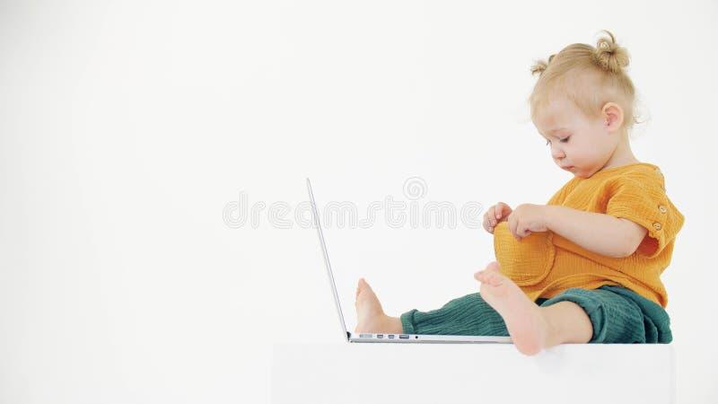 Das lustige Baby-Mädchen schaut in ihre leere Tasche, während es auf dem Laptop sitzt stockfotos