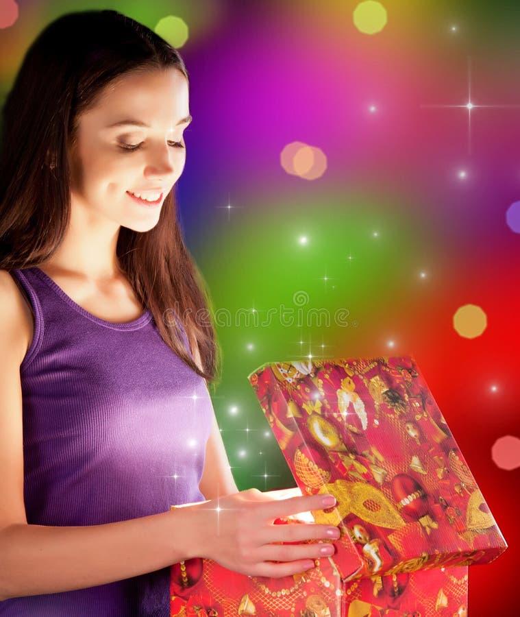 Das Mädchen öffnet das Geschenk lizenzfreies stockbild