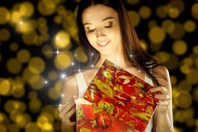 Das Mädchen öffnet das Geschenk stockbilder