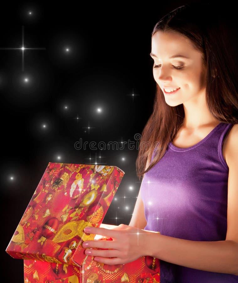 Das Mädchen öffnet das Geschenk stockfotos