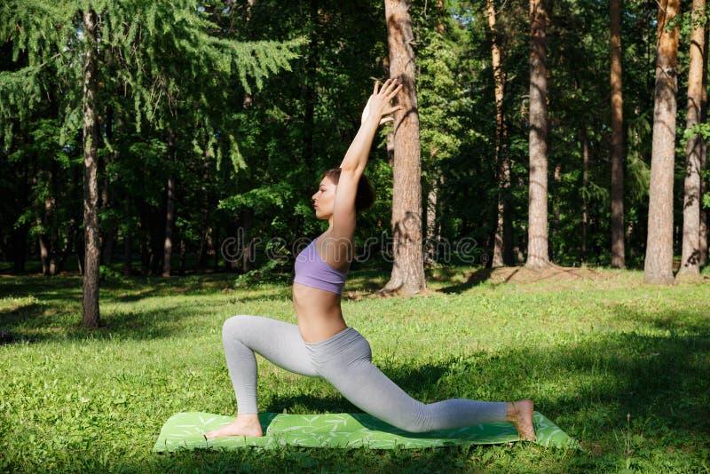 Das Mädchen übt Yoga im Park an einem sonnigen Tag lizenzfreie stockfotografie