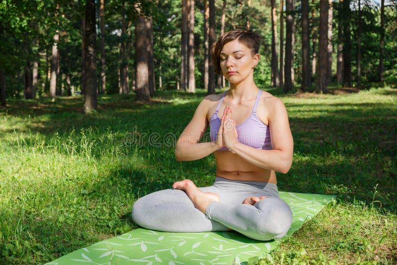 Das Mädchen übt Yoga im Park an einem sonnigen Tag lizenzfreies stockfoto