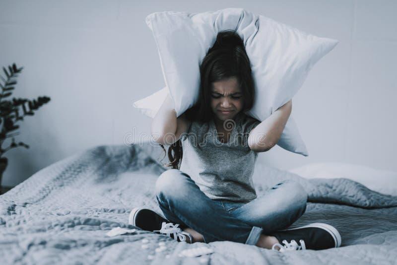 Das Mädchen, das Abdeckungen im Schneidersitz sitzt, gehen mit Kissen voran lizenzfreie stockfotografie