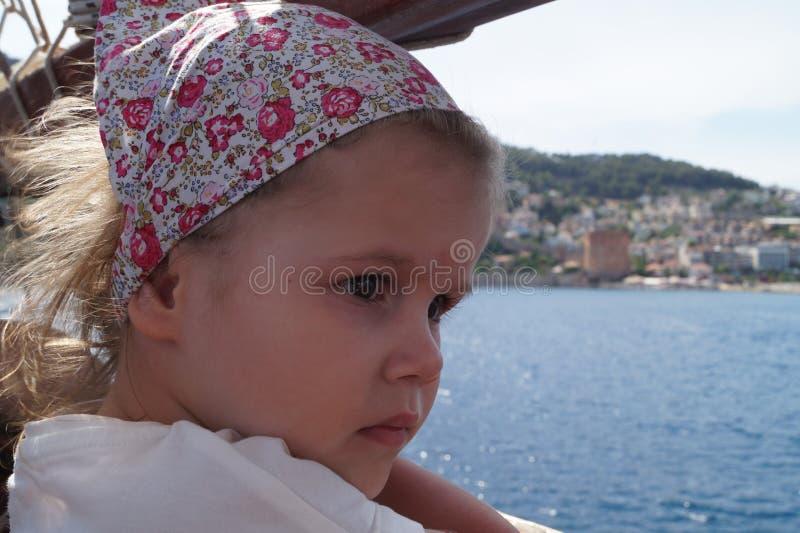 Das Mädchen auf dem Schiff in einem Kopftuch genießt die Ansicht stockfotos