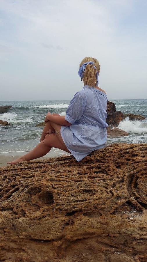 Das Mädchen auf dem Strand, die Blondine durch das Meer stockfotografie