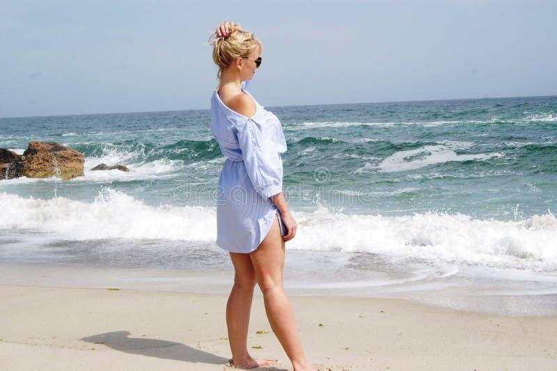 Das Mädchen auf dem Strand, die Blondine durch das Meer Mädchen im blauen Kleid lizenzfreies stockfoto