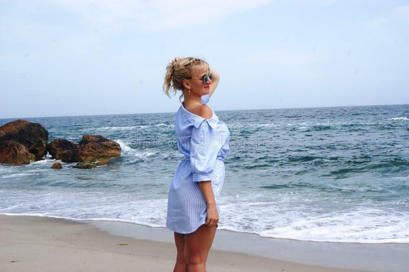 Das Mädchen auf dem Strand, die Blondine durch das Meer Mädchen im blauen Kleid lizenzfreies stockbild