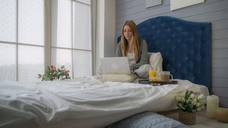 Das Mädchen auf einem Bett, das mit einem Laptop und einem Frühstück arbeitet stockfoto