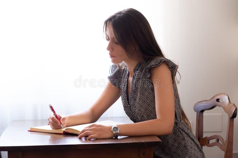 Das Mädchen, das auf einem Stuhl sitzt, schreibt in ihr Tagebuch lizenzfreies stockfoto
