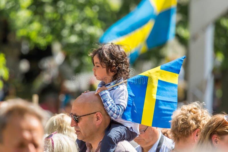 Das Mädchen, das auf a sitzt, bemannt die Schulter, die eine schwedische Flagge hält lizenzfreie stockbilder
