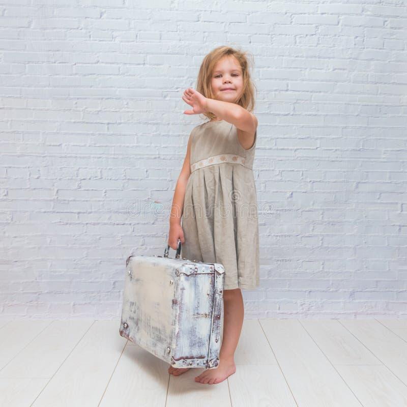 Das Mädchen, Baby im Kleid auf weißem Backsteinmauerhintergrund mit Anzug lizenzfreies stockbild