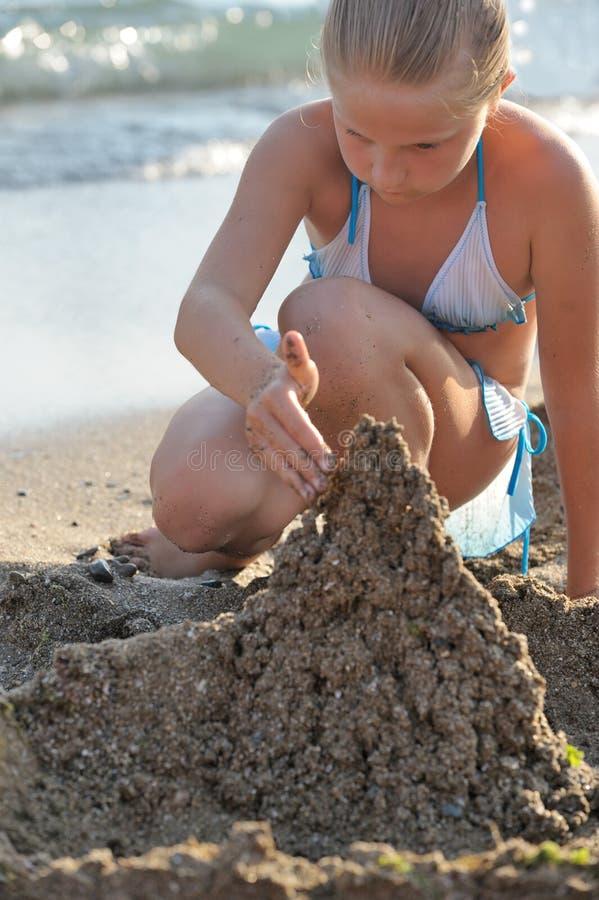 Das Mädchen baut Sandschloß auf stockbild