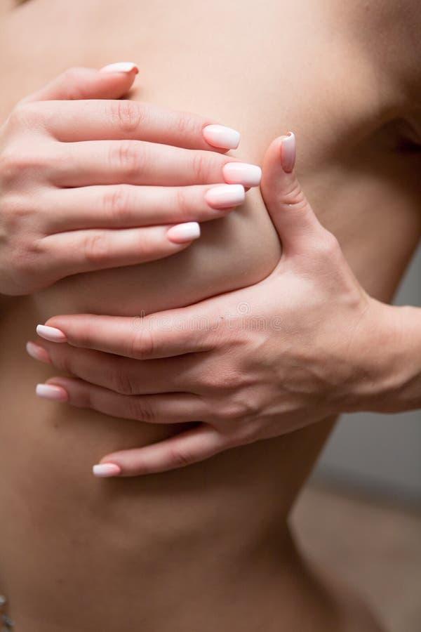 Das Mädchen bedeckte ihren nackten Kasten mit den schönen Händen stockfotografie