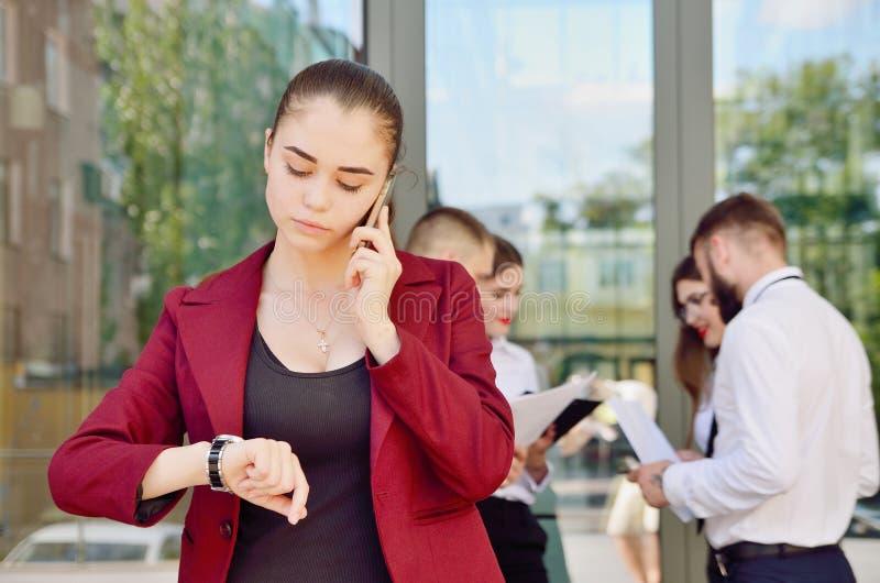 Das Mädchen betrachtet die Armbanduhr Junges Team der Büroarbeit lizenzfreie stockfotos