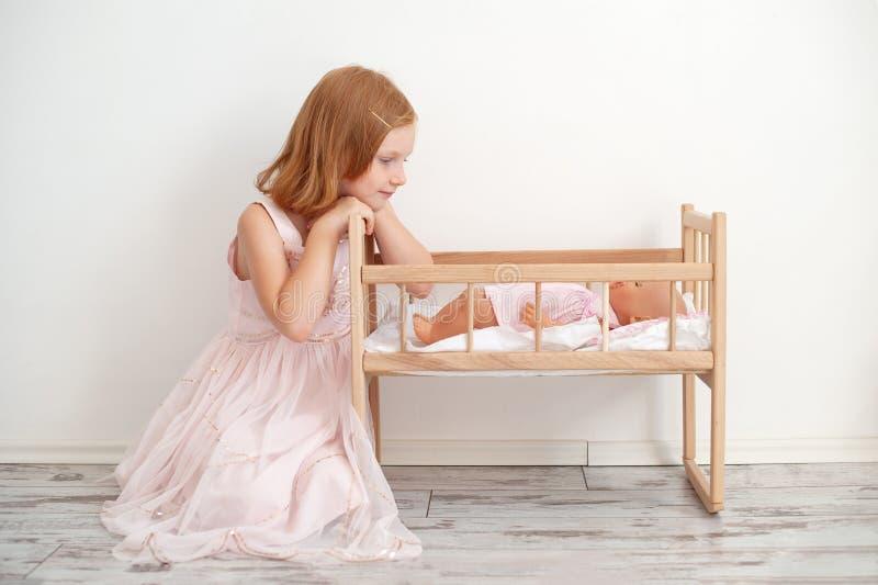 Das Mädchen betrachtet die Puppe in der Krippe lizenzfreie stockbilder
