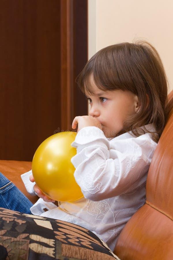 Das Mädchen bläst einen Ballon auf. lizenzfreie stockbilder