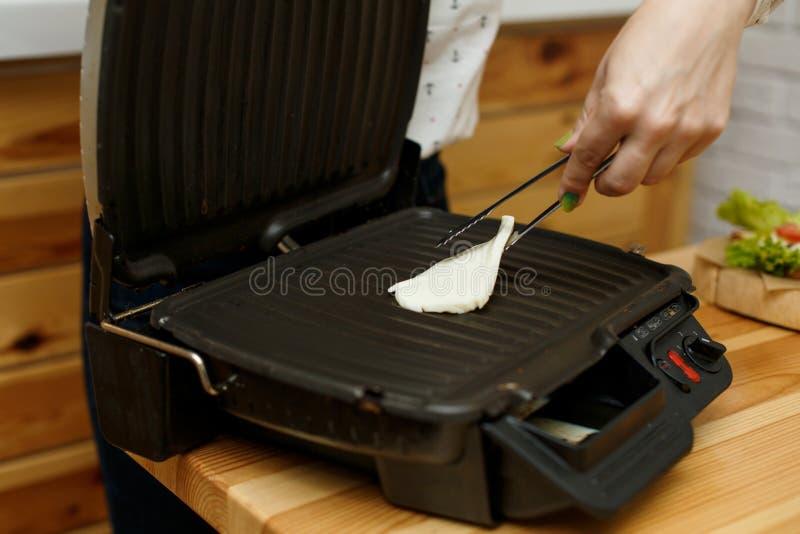 Das Mädchen brät den gegrillten Käse Geschmolzener K?se stockfoto