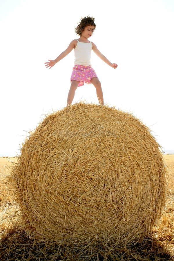 Das Mädchen, das über dem runden Weizen spielt, trocknete Ballen stockbild