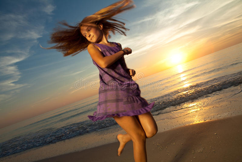 Das Mädchen, das auf schönen Strand springt und tanzt. stockfotos