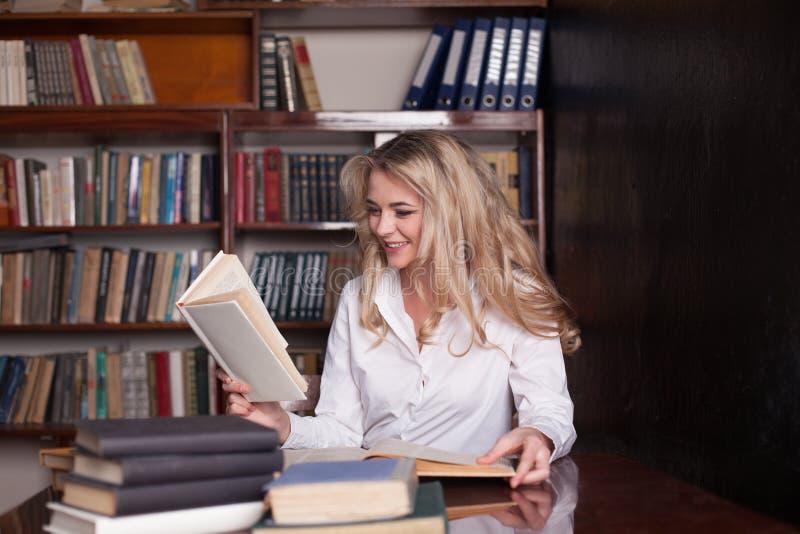 Das Mädchen, das in den Bibliothekslesebüchern sitzt, bereitet sich für die Prüfung vor stockfoto