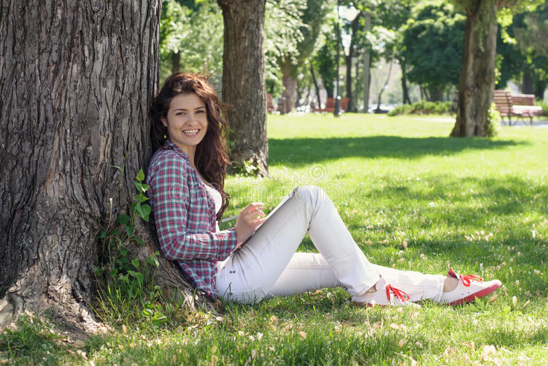 Das Mädchen, das im Park auf dem Gras sitzt und zeichnet lizenzfreie stockfotos