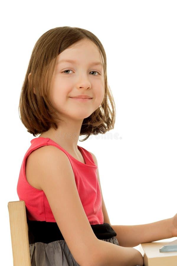 Das Mädchen, das am Tisch sitzt lizenzfreie stockbilder