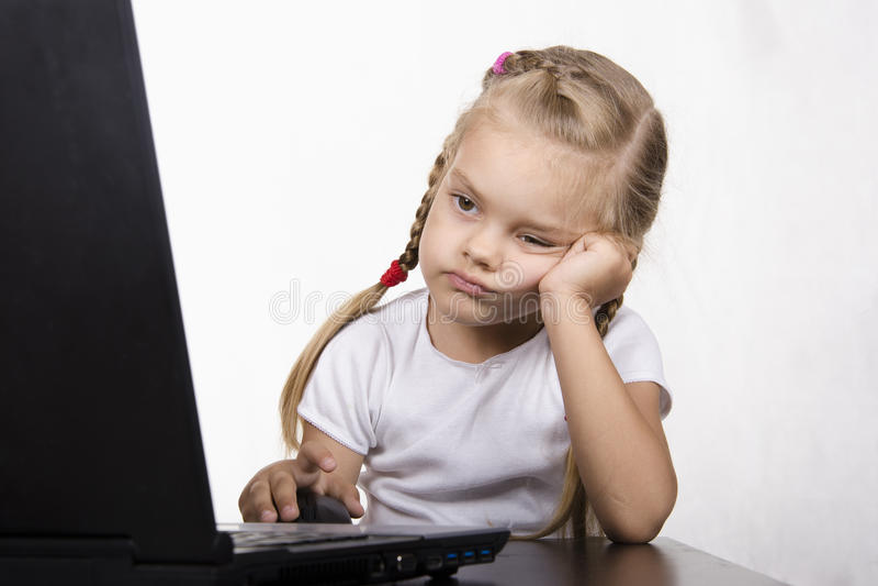 Das Mädchen, das am Tisch und am laufenden Laptop sitzt stockfotos