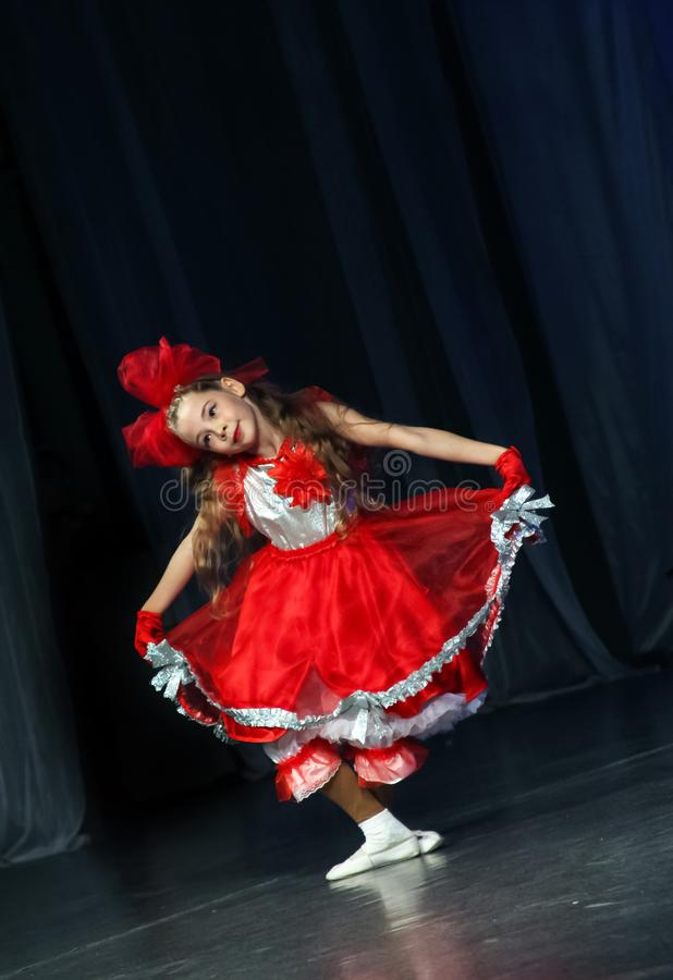 Das Mädchen in den roten Kleidertänzen auf einem Szenentanz der Puppe und der Inspektion lizenzfreies stockbild