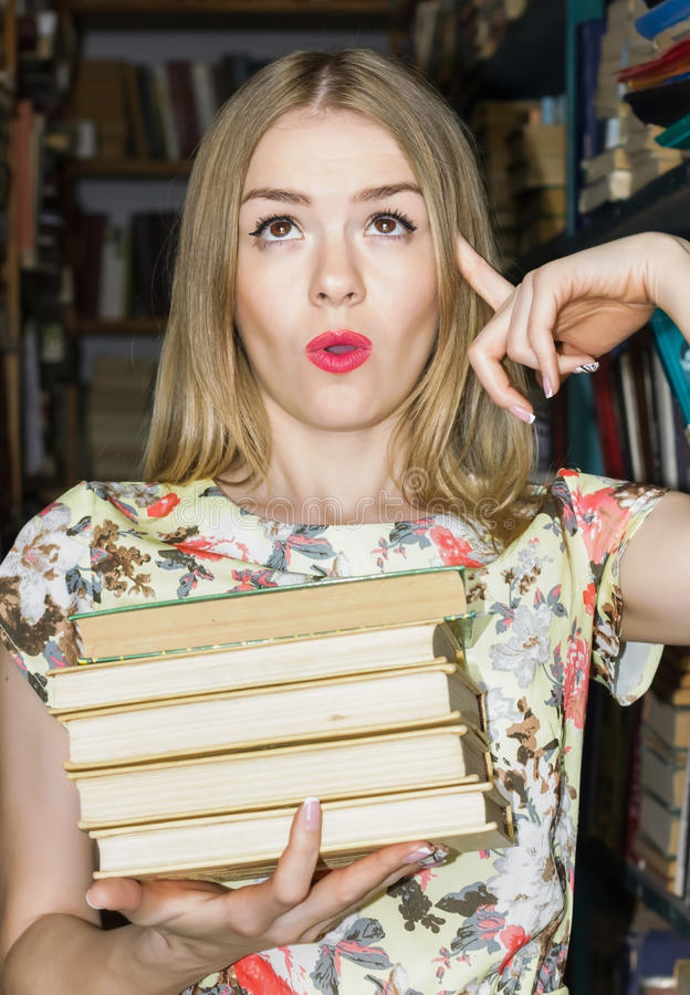 Das Mädchen an der Bibliothek mit den Büchern, die Gefühlerstaunen s ausdrücken stockfotografie