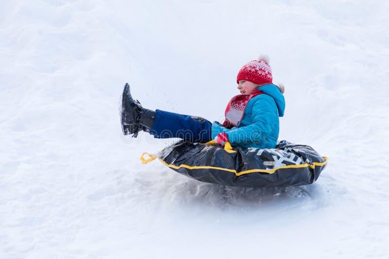 Das Mädchen in der blauen Kleidung mit rotem Hut und dem Schal, die vom Hügel bedeckt mit einem Schnee auf dem schwarzen Gummirin lizenzfreies stockbild