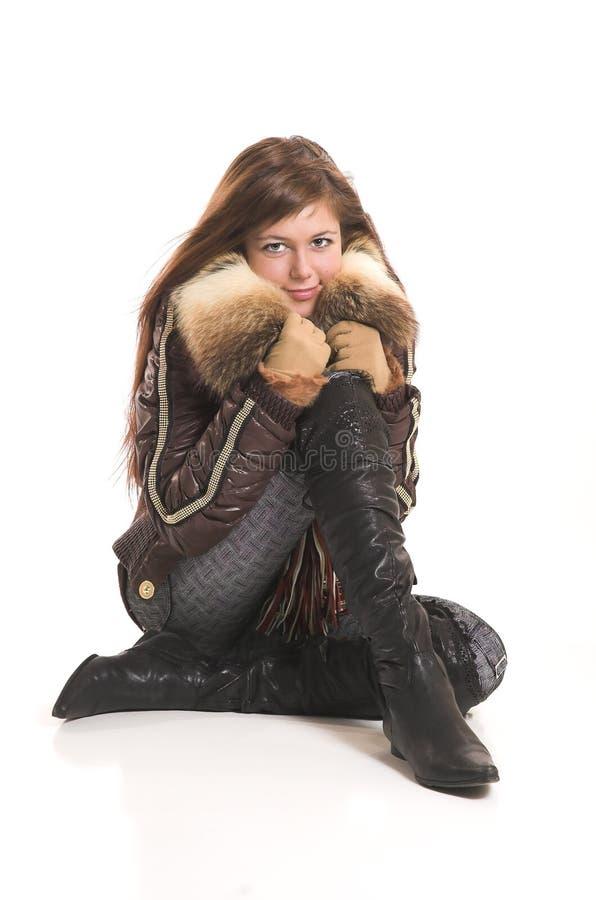 Das Mädchen in der Winterkleidung sitzt lizenzfreies stockfoto
