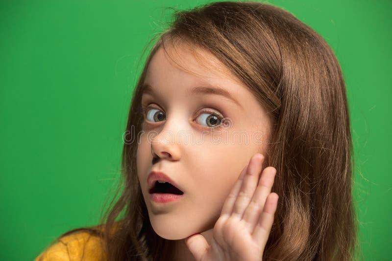 Das Mädchen des jungen jugendlich, das ein Geheimnis hinter ihr flüstert, überreichen grünen Hintergrund stockbild