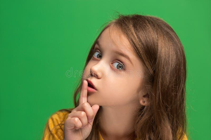 Das Mädchen des jungen jugendlich, das ein Geheimnis hinter ihr flüstert, überreichen grünen Hintergrund lizenzfreie stockbilder