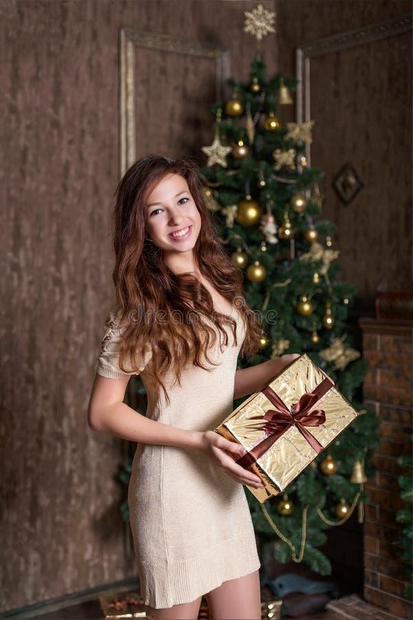 das Mädchen echt froh lächelnd mit einem Weihnachtsgeschenk in ihren Händen steht in einem Goldklassischen Weinlesekleid lizenzfreie stockfotografie