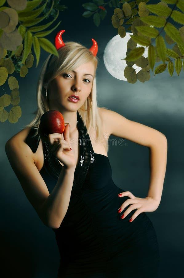 Das Mädchen ein Dämon mit einem magischen Apfel lizenzfreie stockbilder