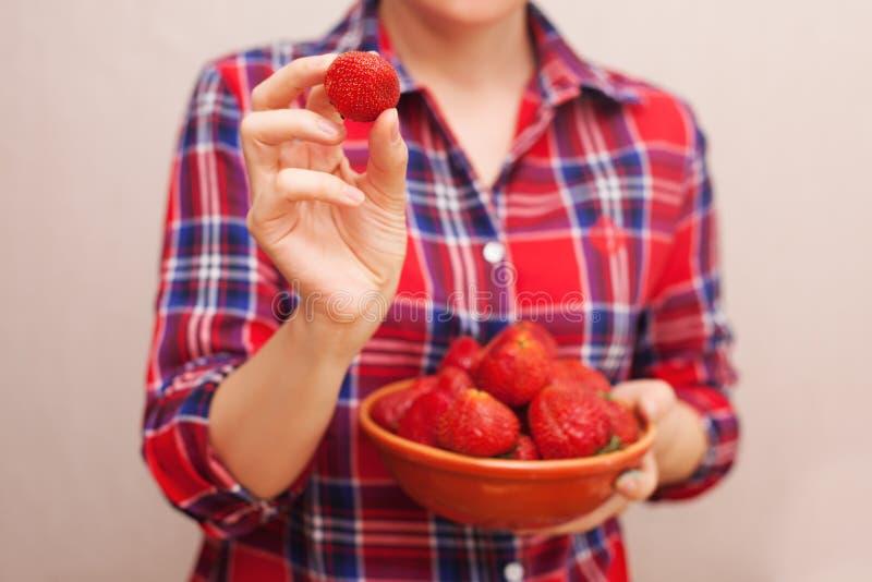 Das Mädchen in einem roten Hemd demonstriert eine schöne rote Erdbeere stockfoto