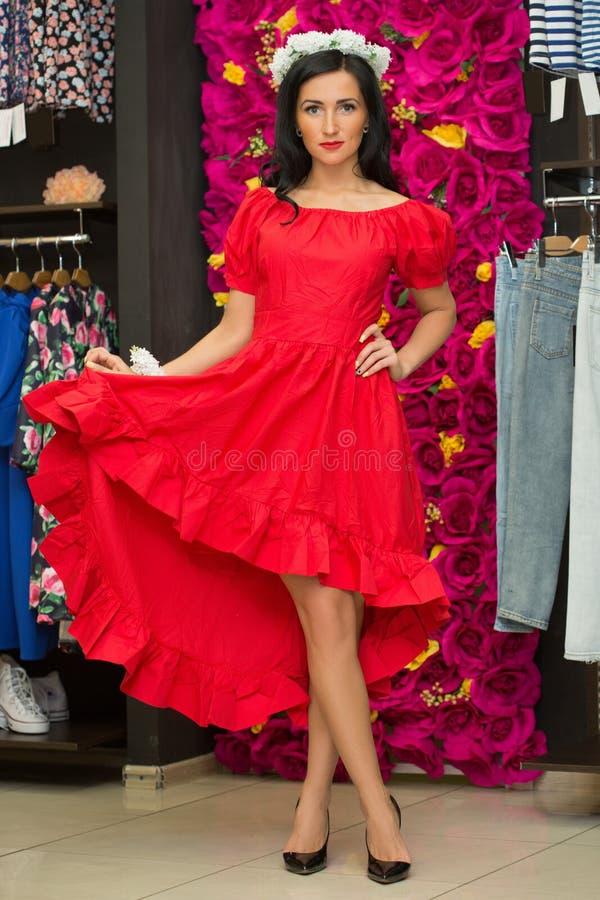 Das Mädchen in einem roten Kleid in einem Bekleidungsgeschäft lizenzfreie stockfotografie