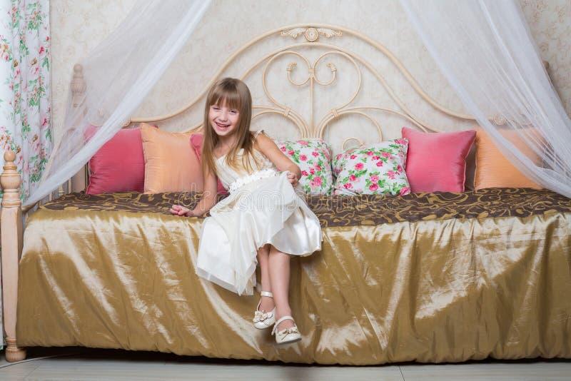 Das Mädchen in einem schönen Kleid sitzt auf dem Bett lizenzfreies stockfoto