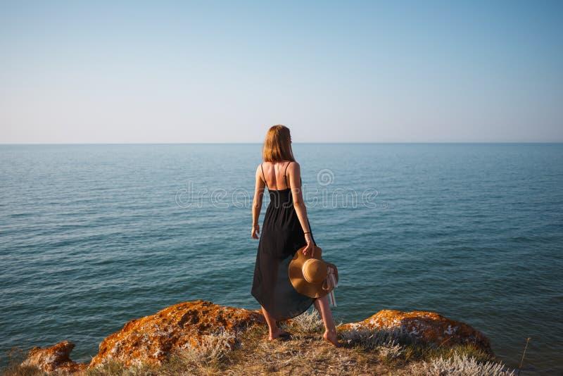 Das Mädchen in einem schwarzen Kleid und in einem Hut auf einem felsigen Strand betrachtet das Meer stockbilder