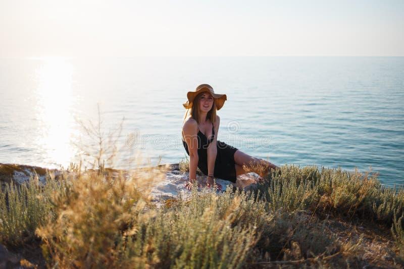 Das Mädchen in einem schwarzen Kleid und in einem Hut auf einem felsigen Strand betrachtet das Meer lizenzfreie stockfotos