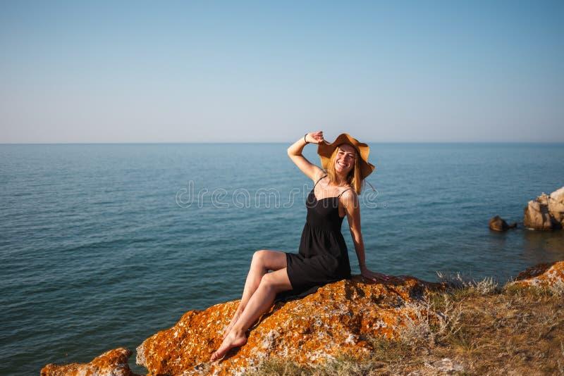 Das Mädchen in einem schwarzen Kleid und in einem Hut auf einem felsigen Strand betrachtet das Meer lizenzfreie stockbilder
