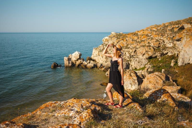 Das Mädchen in einem schwarzen Kleid und in einem Hut auf einem felsigen Strand betrachtet das Meer lizenzfreie stockfotografie