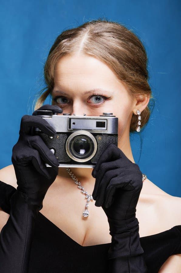 Das Mädchen in einem schwarzen Kleid und langen Handschuhen des Abends hält eine weit reichende Kamera des Filmes in ihren Händen lizenzfreie stockfotografie