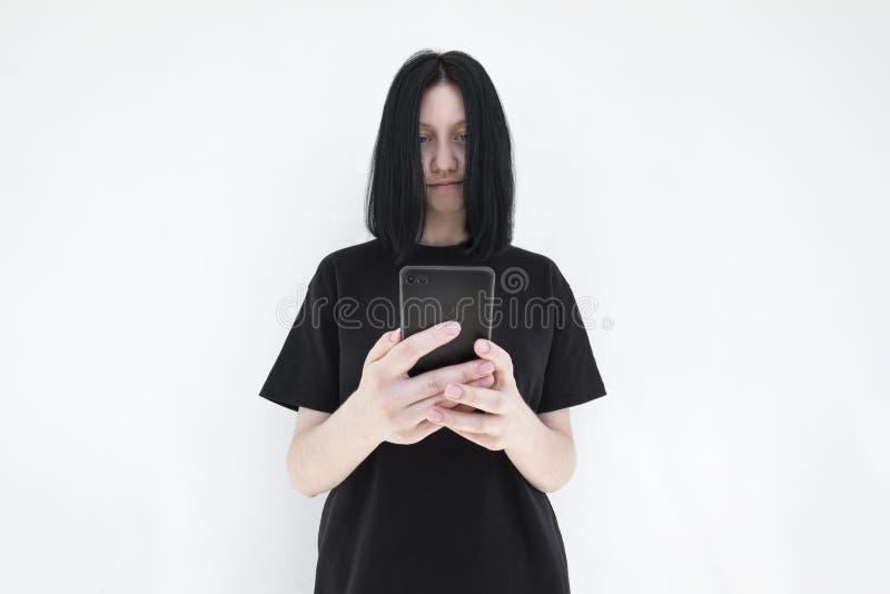Das Mädchen in einem schwarzen Kleid und mit dem schwarzen Haar mit einem Smartphone in ihren Händen auf einem weißen Hintergrund lizenzfreies stockfoto